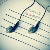 Hörlurar som simulerar musikaliska anmärkningar och texten fiesta de la mus Arkivfoton