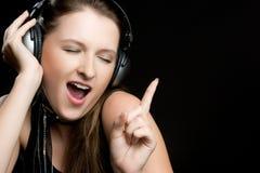 hörlurar som sjunger kvinnan Arkivfoton