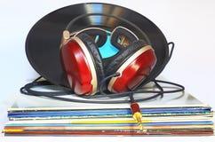 Hörlurar som vilar på en bunt av vinyl Arkivfoton