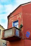 Hörn av en gammal röd byggnad med en balkong royaltyfri foto