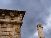 Hörn av en gammal Venetian vägg med att förbluffa garneringar och det gamla kyrkliga tornet i bakgrunden royaltyfri fotografi