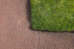 Hörn av grön gräsmatta som är närgränsande till den röda grov asfaltbeläggningbanan - tankeskapelse Arkivbild