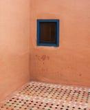Hörn av väggen med det belade med tegel golvet och ett enkelt fönster Royaltyfri Bild