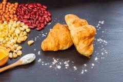 Hörnchen-Brot, frisches Ei im Mehl und Erdnüsse und rote Linsen und Mais auf schwarzer hölzerner Tafel Lizenzfreies Stockfoto