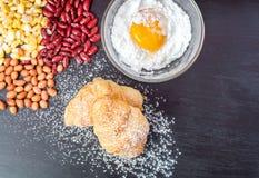 Hörnchen-Brot, frisches Ei im Mehl und Erdnüsse und rote Linsen und Mais auf schwarzer hölzerner Tafel Stockfotos