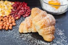 Hörnchen-Brot, frisches Ei im Mehl und Erdnüsse und rote Linsen und Mais auf schwarzer hölzerner Tafel Lizenzfreie Stockbilder
