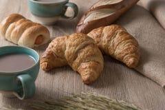 Hörnchen mit Brot und Kaffeetasse auf hölzernem Hintergrund Lizenzfreies Stockbild