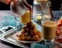 Hörnchen mit Schokolade und Kaffee auf dem Behälter Stockfoto