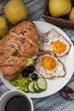 Hörnchen-Sandwich mit Fried Eggs, Gurken und Oliven, Früchte und Frischgemüse und Tasse Kaffee auf weißer Platte Lizenzfreie Stockbilder