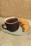 Hörnchen und eine Tasse Tee Stockbild