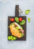 Hörnchensandwich mit geräucherten Fleisch Prosciuttodi Parma, sonnengetrockneten Tomaten, frischem Spinat und Basilikum auf dunkl Lizenzfreies Stockfoto