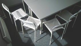 Hörnet av en stor vit konferenstabell och fyra stolar bredvid honom Nära fönster och element Begreppet av affären arkivbild