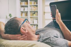Hörselskadad man med bärbara datorn och mobiltelefonen Arkivfoton