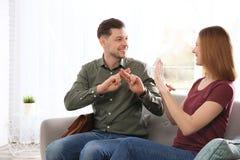 Hörselskadade vänner som använder teckenspråket för kommunikationen på soffan i rum royaltyfria bilder