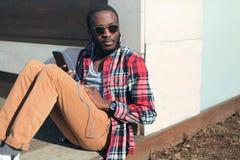 Hört junges afrikanisches Mannsitzen des Modeporträts Musik Stockfotografie