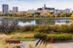 Höst. Ensam bänk vid floden med en sikt av Saskatoon downt Arkivfoto