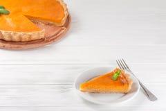 Höst för efterrätt för pumpapaj läcker hemlagad Stycke av den traditionella kakan med klippt pumpa på vit träbakgrund Vegetarian  Royaltyfri Foto