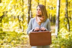 Höst-, natur- och folkbegrepp - stående av den härliga le kvinnan med den bruna resväskan i höstnatur royaltyfria bilder