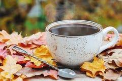 Höst nedgångsidor, varm ånga kopp kaffe på trätabellbakgrund Säsongsbetonat morgonkaffe, söndag koppla av royaltyfri bild