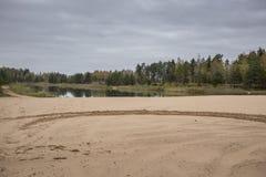 Höst på en liten skogsjö med den sandiga stranden Royaltyfri Bild