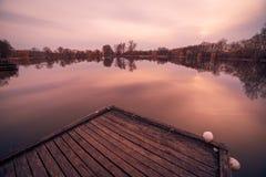 Höst sjö med en träpir och en härlig reflexion royaltyfri bild
