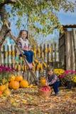 Höst som samlar äpplen på lantgården För barn frukt mot efterkrav i korgen utomhus- roliga ungar arkivbild
