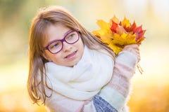 Höst Stående av en le ung flicka som rymmer i hennes hand en bukett av höstlönnlöv Arkivfoton