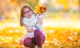 Höst Stående av en le ung flicka som rymmer i hennes hand en bukett av höstlönnlöv arkivbild
