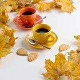 Höst Två koppar kaffe och kakor i formen av tjänstledigheterna Royaltyfri Foto