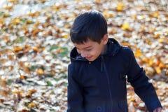 Höstbarns kläder, ett leende på framsidan av lite pojken som går i natur i nedgången, en skolpojke i royaltyfri bild