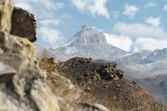 Höstberglandskapet av gulnat lutningar och gräs i bergen med epos vaggar och särar av snö-täckte lutningar arkivbilder