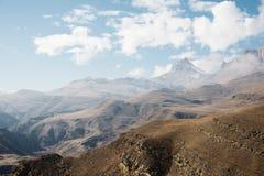 Höstberglandskapet av gulnat lutningar och gräs i bergen med epos vaggar och särar av snö-täckte lutningar royaltyfria foton