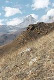 Höstberglandskapet av gulnat lutningar och gräs i bergen med epos vaggar och särar av snö-täckte lutningar arkivfoto