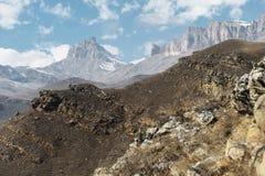 Höstberglandskapet av gulnat lutningar och gräs i bergen med epos vaggar och särar av snö-täckte lutningar royaltyfria bilder