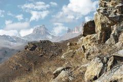Höstberglandskapet av gulnat lutningar och gräs i bergen med epos vaggar och särar av snö-täckte lutningar royaltyfri foto