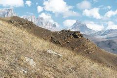 Höstberglandskapet av gulnat lutningar och gräs i bergen med epos vaggar och särar av snö-täckte lutningar arkivbild