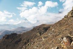 Höstberglandskapet av gulnat lutningar och gräs i bergen med epos vaggar och särar av snö-täckte lutningar fotografering för bildbyråer