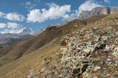 Höstberglandskapet av gulnat lutningar och gräs i bergen med epos vaggar och särar av snö-täckte lutningar royaltyfri bild