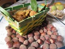 Hösten bär frukt med hasselnötter och den vide- korgen av torkade fikonträd på tabellen Äpplen, päron och plommoner i bakgrund Royaltyfri Foto
