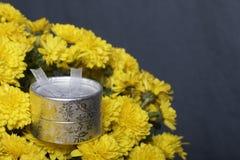 Hösten blommar i en kruka Gul chrysanthemum Nästa gåva i en silverask på en grå färgbakgrund royaltyfri fotografi