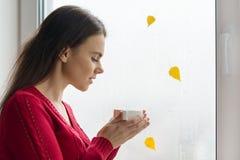 Hösten i fönstret, står en ung flicka nära fönstret med regndroppar och ett gult blad som dricker kaffe royaltyfria foton