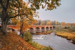 Hösten landskap Den gamla tegelstenbron över den Venta floden in royaltyfri fotografi