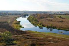 Höstfält och smal flod med reflexioner av moln Royaltyfria Bilder