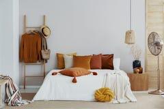 H?stf?rger i det ljusa naturliga sovrummet med tr?brytningar, kopieringsutrymme p? den tomma v?ggen royaltyfria foton