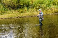 Höstfiske på en liten flod arkivfoton