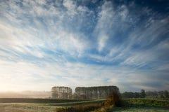 Höstgryningliggande över frostiga dimmiga fält Royaltyfri Bild