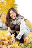 Höstkvinna som spelar med färgrika nedgångsidor Fotografering för Bildbyråer