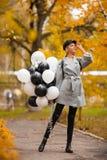 Höstkvinnan i höst parkerar med ballonger Modeflicka i grå färglag arkivbild