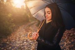 Höstkvinnan i höst parkerar med det svarta paraplyet Arkivfoton