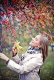 Höstkvinnan som är lycklig i nedgång, parkerar att se runt om att ha gyckel som ler i härlig färgrik skoglövverk Royaltyfria Foton